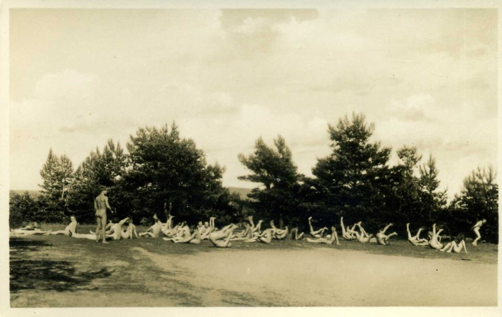 Black and white photograph of nudists exercising outdoors at nudist camp in Berlin