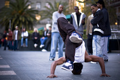 Color image of a B-boy performing a form of head in front of a crowd