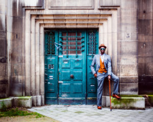A modern Sapeur leans against a vibrant colored door, his foot propped up behind him while holding a cane.
