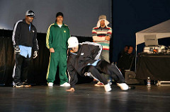 Color image of Ken Swift performing at the B-boy Contest with three other performers observing