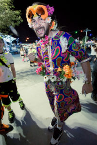 Raver at EDC 2012. He is wearing a colorful tunic and is covered in flowers and has some sort of orange furry hat on.