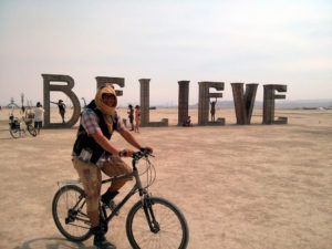 A 'Burner' cycling around the desert site filled with large scale art installations; this image shows a n installation that spells out the word 'believe' in large letters