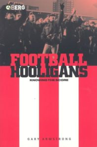 The cover to Gary Armstrong's book, Football Hooligans: Knowing the Score, which has red and white stripes with a grey scale depiction of hooligans