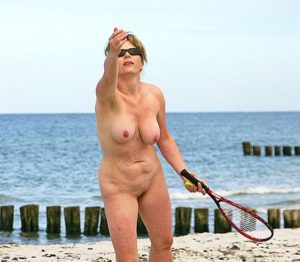 Image of woman playing badminton at a nudist camp