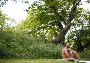 Image of a nudist man relaxing by a tree