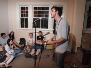 A person singing and playing a guitar at a house show with people sitting on the carpeted floors.