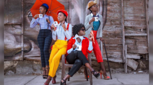 Four Sapeuses pose with mugs, each dressed in bright, stylish clothes, looking off to the side. Two sit, while the other two stand, one holding an umbrella and the other leaning on a cane.