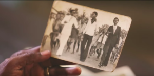 A man holding a black and white picture of the generation before him dressed as Sapeurs