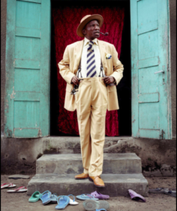 A Sapeur stands outside his family home dressed in a suit and leather shoes while the flip flops of his family are strewn around him