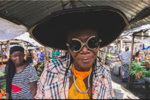 Musa Umpalaba smiles into the camera while at the local market, next to a woman who is dressed in simple clothes
