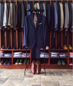 A picture of a closet with designer clothes hanging up inside. In front of them hangs a suit matched to a tie and a pair of leather shoes.