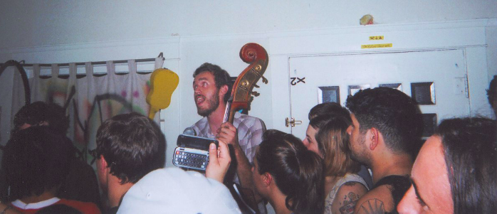 Andrew Jackson Jihad playing a show in long beach in a crowded living room. A bass peaks out from above the heads.