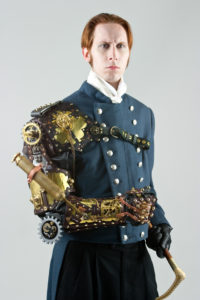 Victorian inspired dark teal with double rows of gold buttons down the front, with a mechanical structure encasing the right arm and holding a cane with a carved wooden birdhead cane