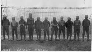 The British soccer team stands in front of a goal wearing gas masks during World War I