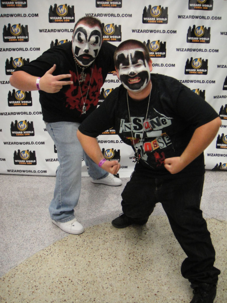 Two young Juggalos at an Insane Clown Posse gathering with clown makeup and ICP t-shirts standing in front of a backdrop.