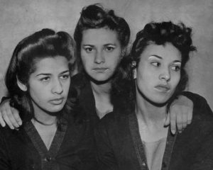 Black and white picture of 3 Pachucas with dramatic eye make up held in prison.