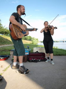 """Two people, one Chris Clavin, playing a guitar and violin outside. Chris' guitar reads """"Weapon of Mass Destruction"""""""