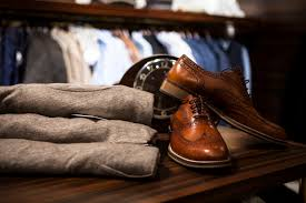 A pair of leather shoes with some folded clothes on a table with a clothing rack in the background