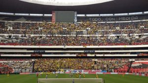 Home hooligans wearing yellow fill the seats behind their goal to root for their team in the Mexican League at Estadio Azteca