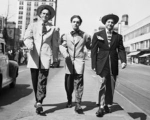 Black and white photo of Pachucos in zoot suites strutting down the street toward the camera