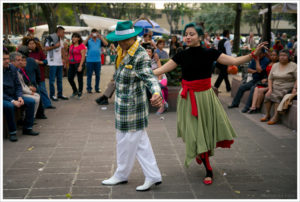 Colored photo of a man wearing a turquoise zoot suit and a woman in a black top and green skirt dancing in a square in Mexico City while onlookers observe