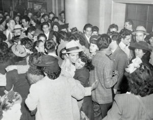 Black and white picture of a crowded room of rioters celebrating after being acquitted.