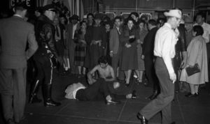 Black and white photo of a Pachuco who was stripped of their zoot suit while others, including the police, surround them and watch.