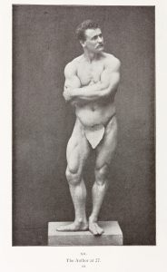 Eugen Sandow posing on a platform, arms crossed