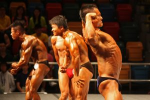 Bodybuilders flexing in concave and convex shapes at a competition
