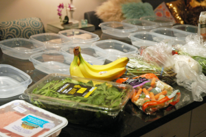 Food packages and plastic containers laid out on a counter before meal preparation
