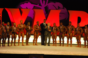 Bodybuilding competitors wearing medals lined up on the Mr. Olympia stage