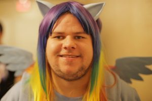 Photo of an adult male Brony in a rainbow wig, cat ears, and pony wings similar to the characters on the show.