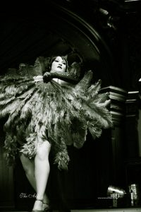 Black and white photo of burlesque performer mid-performance covered by giant feather fans