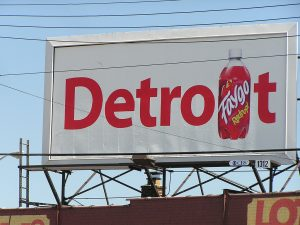 "A billboard with the word Detroit with the ""I"" replaced with an image of Faygo soda."