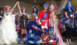 Photoshoot at BronyCon in which a group of people are dressed as characters from the show. For example, one woman is dressed in all pink with a horn and a man is dressed in a uniform and a horn