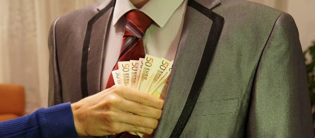 Image of a man in a suit chest and arms only) having money put into his jacket pocket
