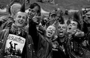 "Group of people in the punk subculture posing for a picture. They are all sporting mohawks and look to be happy. They are wearing leather jackets with studs, and one of them has a lip piercing. The image is in black and white and one person is throwing up a ""rock on"" sign and another a ""peace"" sign with their hands."