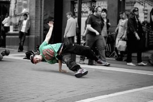 A young man break-dances in the street. He uses a difficult move of balancing his entire body on the strength of one hand.