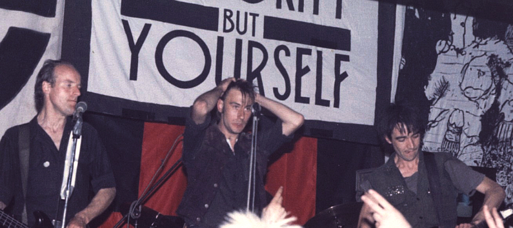 Punk group Crass performs under the banner