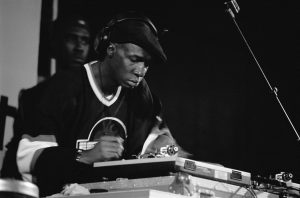 A black and white photograph of Grandmaster Flash, one of the original DJ's, scratches a disc on stage at a performance