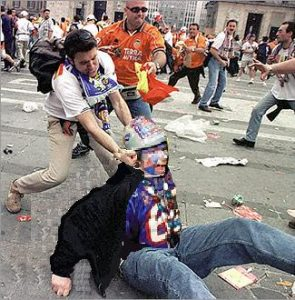 One hooligans punches another in the streets during a riot between two opposing teams