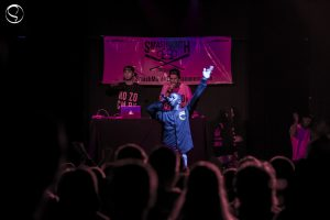 Hopsin stands on stage performing at a small, underground hip-hop club. Behind him stand sound mixers and the rest of his group.