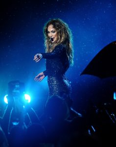 Pop star Jennifer Lopez stands on stage and points into the crowd.