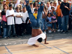 "Image of a B-boy performing a form of ""freeze"" in public in front of a large crowd"