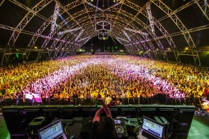 Thousands of people cheer and dance for DJ Bassnectar at Coachella. The image is from the perspective behind the DJ, and shows Bassnectar with his hands raised about his computer and soundboard as he dances and looks into a very large crowd in Coachella's (notable) Sahara tent where most EDM acts perform. The audience is showered in yellow and pink light below the tent's dark atrium. The crowd reaches far back in the tent and possibly beyond.