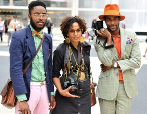 3 people stand with vintage but clean-cut suit outfits on holding cameras. They are wearing bright colors or eccentric jewelry.