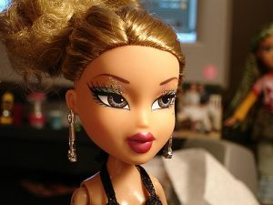 A headshot of a Bratz doll with heavy makeup and jewelry.