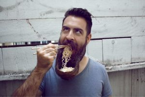 Graphic shows a man whose beard has been matted into a bowl shape and is shoveling ramen noodles from it into his mouth using chopsticks. He looks up in a way that could mean he sees his actions as ironic.