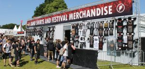 "Merchandise booth at a concert showing many t-shirts on a wall, with people gathering around the fenced off area with the seller inside. The banner at the top of the booth says ""Band shirts and festival merchandise"""