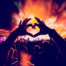Person making heart hands at a music festival